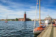 Båtar vid Riddarholmens kaj med Stadshuset i Stockholm
