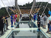 ZHANGJIAJIE, CHINA - JUNE 25:<br /> <br /> A car drives over glass-bottomed bridge for a safety test at Zhangjiajie Grand Canyon on June 25, 2016 in Zhangjiajie, Hunan Province of China. World\'s tallest and longest glass-bottomed bridge has been completed and took a global broadcast through television and internet medias to show its safety. More than thirty citizens and visitors thumped the bridge with hammer in the test event. <br /> ©Exclusivepix Media