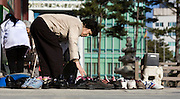 A Woman bends to get her shoes at the Buddhist Hall of the Great Hero, Jogye-sa Temple, Seoul...Hall of the Great Hero or Daeung-jeon at Jogye-sa Buddhist Temple, Seoul, South Korea. Jogyesa is the main temple of the Jogye Order of Korean Buddhism, and has a important part in Seon Buddhism. Located in Gyeonji-dong, Jongno-gu within in the old city of Seoul.
