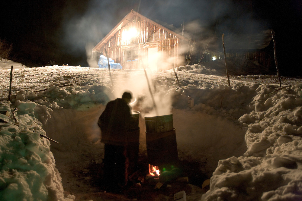 USA, Alaska, Takotna, Young man checks on hot water supply heated by wood-burning barrel stoves on winter night at Takotna checkpoint during 2005 Iditarod sled dog race