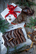 Christmas background with box of homemade mostaccioli, neapolitan traditional cookies made with cloves, star anise, cocoa powder, orange, tangerine and lemon peel.
