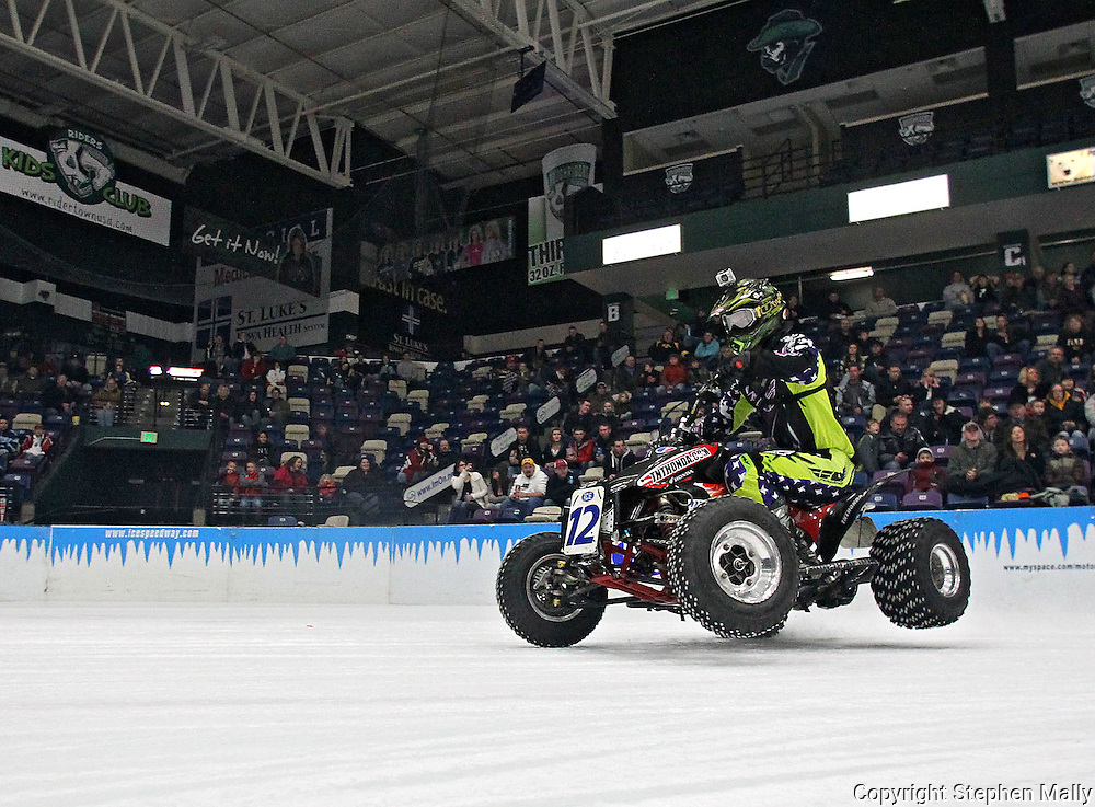 Justin Ebbing (12) of Quiney, Illinois balances on two wheels while coming into turn three during an Unlimited Outlaw Quads heat at the 35th Annual World Championship ICE Racing Series held at the Cedar Rapids Ice Arena at 1100 Rockford Road SW in Cedar Rapids on Saturday evening January 15, 2011.