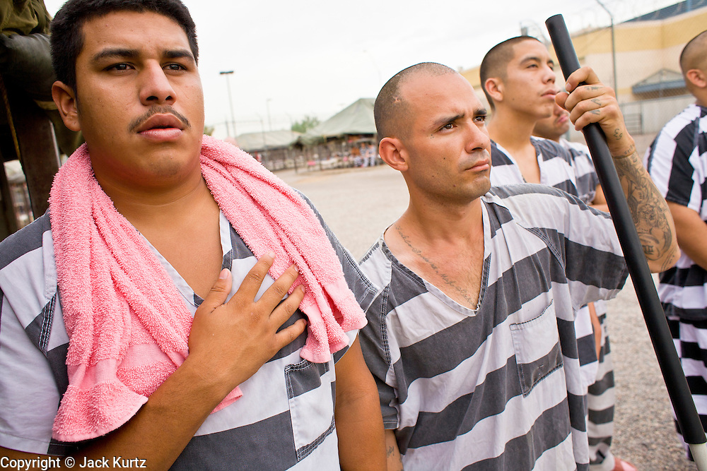 "17 JULY 2006 - PHOENIX, AZ: Inmates CHRISTIAN MIRANDA (LEFT), BERNIE VALENZUELA, and IRVING ORTIZ, stand with their hands over their hearts while the National Anthem is played in ""Tent City"" in the Maricopa County Jail in Phoenix, AZ. There are about 650 inmates living in the tents. Maricopa County Sheriff Joe Arpaio recently started playing the Star Spangled Banner and God Bless America twice a day in the county jails. Inmates are encouraged, but not forced, to stand at attention with their hands over their hearts, when the music is played. When asked about the new policy Arpaio said, ""Our men and women are fighting and dying for our country in Iraq and that's the least these inmates can do."" In 2011, the US Department of Justice issued a report highly critical of the Maricopa County Sheriff's Department and the jails. The DOJ said the Sheriff's Dept. engages in widespread discrimination against Latinos during traffic stops and immigration enforcement, violates the rights of Spanish speaking prisoners in the jails and retaliates against the Sheriff's political opponents.      PHOTO BY JACK KURTZ"