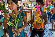 """21 JULY 2013 - BANGKOK, THAILAND: People wait in line to make merit at Wat Mahabut on the first day of Vassa, the three-month annual retreat observed by Theravada monks and nuns. On the first day of Vassa (or Buddhist Lent) many Buddhists visit their temples to """"make merit."""" During Vassa, monks and nuns remain inside monasteries and temple grounds, devoting their time to intensive meditation and study. Laypeople support the monastic sangha by bringing food, candles and other offerings to temples. Laypeople also often observe Vassa by giving up something, such as smoking or eating meat. For this reason, westerners sometimes call Vassa the """"Buddhist Lent.""""          PHOTO BY JACK KURTZ"""