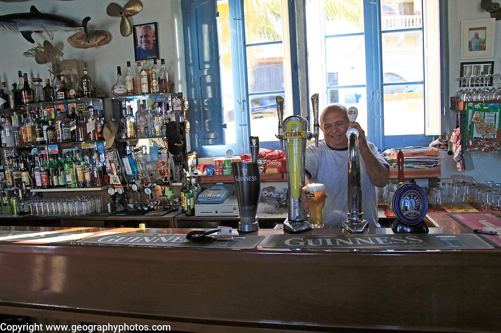 Barman pulling pints of beer Inside Gleneagles Bar pub at Mgarr, Gozo, Malta