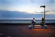 Frankrijk, Le Touquet, 5-9-2005..Jongeren zitten bij het strand aan de zee op een bankje tijdens ondergaande zon, zonsondergang. Romantiek. jongen en meisje, stel, relatie, relatieproblemen, verkering, liefde, verliefdheid. eenzaamheid...Foto: Flip Franssen/Hollandse Hoogte
