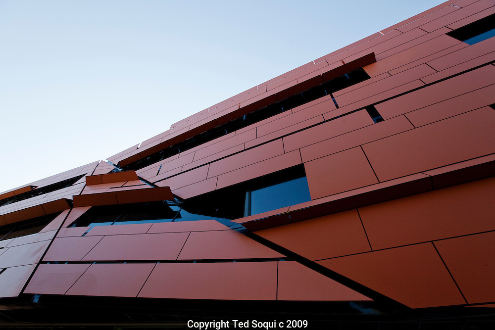 Cahill Center for Astronomy and Astrophysics at California Institute of Technology. The three story 100,000 square foot building was designed by architect Thom Mayne, founder of Morphosis based in Santa Monica, CA. .The unusual building features red/orange colored panels with angled cracks running down the building's sides..The building's address is 1216 California Blvd. 1216, in angstroms, is the wavelength of ultraviolet light emitted by hydrogen atoms..The Cahill building will allow 300 of Caltech's astronomy and astrophysics faculty and grad students to work and teach in.