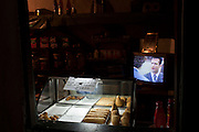 A soap opera goes on tv at a bar with snack displayed in a hot box in  Rocinha slum in Rio de Janeiro, Brazil, Thursday, Feb. 28, 2013. Although Rocinha is technically classified as a neighborhood, many still refer to it as a favela. It developed from a shanty town into an urbanized slum. In November 2011, a security operation was executed where hundreds of police and military patrolled the streets of Rocinha to crackdown on rampant drug dealers and bring government control to the neighborhood.