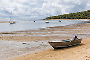 Tinnie dinghy on beach shore at low tide with sailboats in 1770 Seventeen Seventy, Queensland, Australia