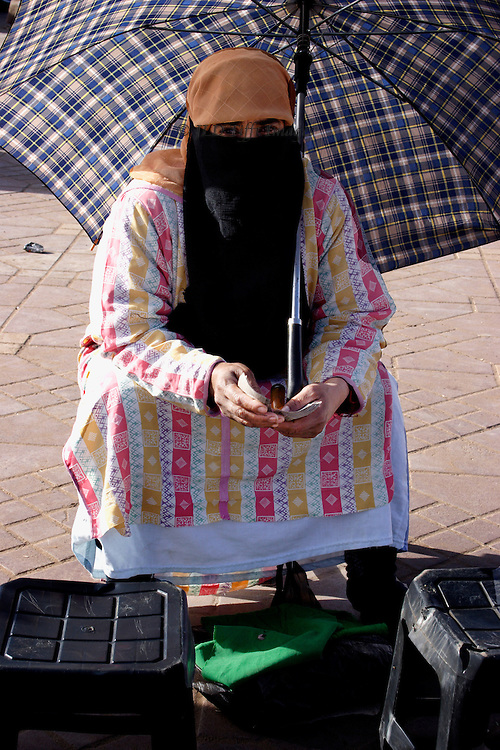 Marrakech: Jemaa el-Fna; seated woman vendor, wearing a birka and shaded by a plaid umbrella, holding a fistful of paper money.   Her eyes look through her mask straight at the camera.