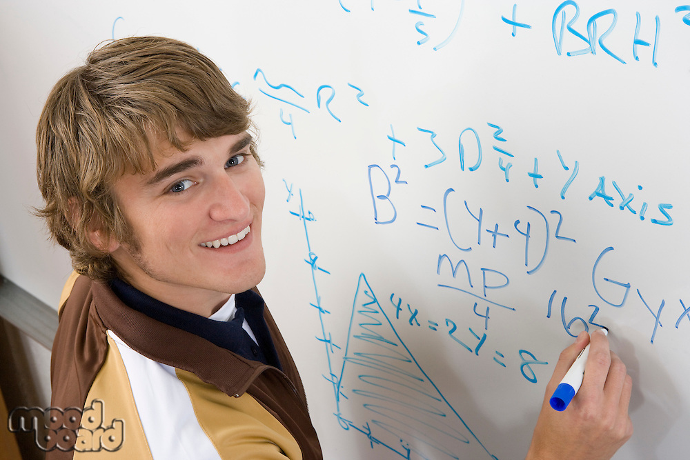 Male student writing maths equations on whiteboard