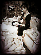 Young Vietnamese woman surrounded by styrofoam boxes filled with bread, slices a single baguette, Hanoi, Vietnam, Southeast Asia
