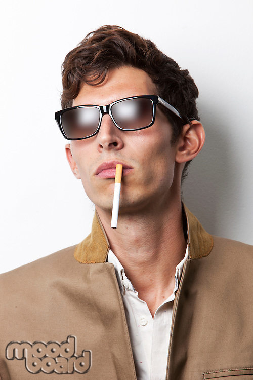 Young man in sunglasses smoking cigarette against white background