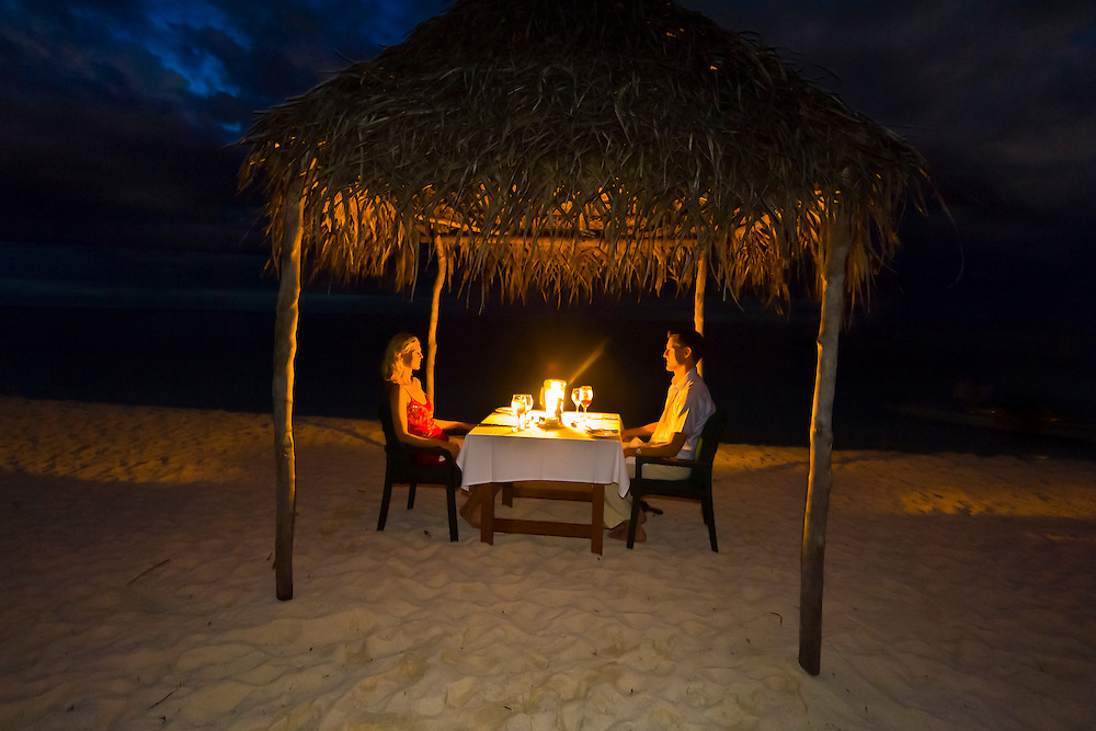 A honeymooning couple enjoy a private dinner on the beach, Vatulele Island Resort, Fiji Islands