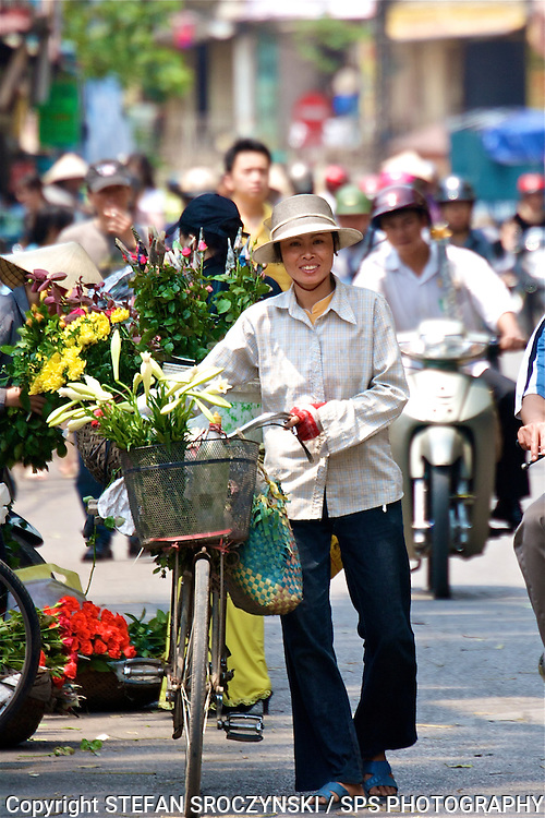 Woman selling flowers from her pushbike on the streets of Hanoi, Vietnam.