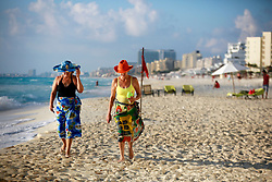 10 Feb 2014. Cancun, Mexico.<br /> Ladies in hats and sarongs walk the tourist beach at Isla Cancun along the Zona Hotelera on the Carribean Sea. <br /> Photo; Charlie Varley/varleypix.com