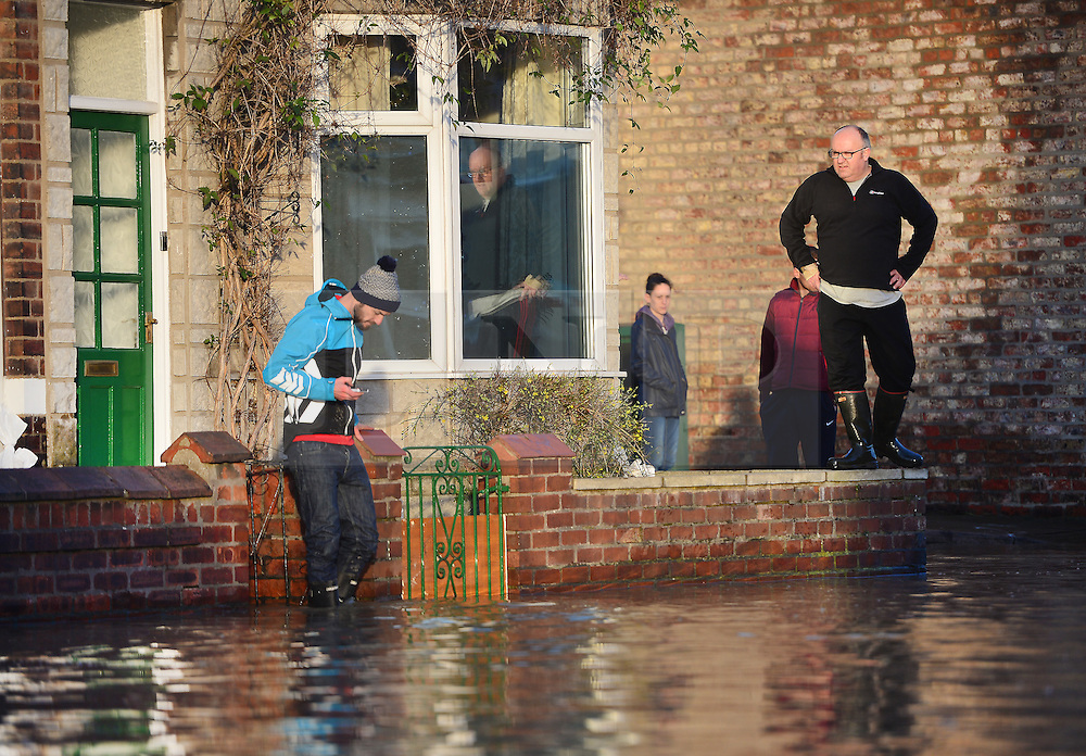 © Licensed to London News Pictures. 27/12/2015. York, UK.  Residents look out from their houses as  flood water rises in Huntingdon Road, York. Large areas of the North of England have been hit by severe flooding following unusually heavy rainfall in December. Photo credit: Ben Cawthra/LNP