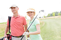 Smiling male and female friends standing at golf course