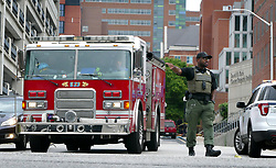 July 5, 2018 - Baltimore, MD, USA - Johns Hopkins security directs traffic after two cancer research buildings at Johns Hopkins Hospital were evacuated due to possible tuberculosis contamination, according to the hospital, on July 5, 2018. The buildings on the 1500 block of Orleans Street were evacuated as the Baltimore City Fire Department investigated the possible release of a small amount of tuberculosis in a bridge between the two buildings. (Credit Image: © Lloyd Fox/TNS via ZUMA Wire)