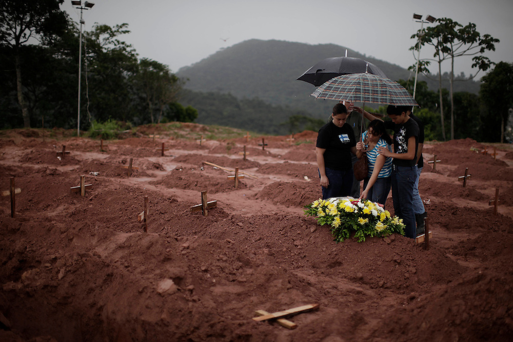 People leave flowers after a burial of a landslide victim in Teresopolis, Brazil, Friday, Jan. 14, 2011. <br /> <br /> A series of flash floods and mudslides struck several cities in Rio de Janeiro State, destroying houses, roads and more. More than 900 people are reported to have been killed and over 300 remain missing in this, Brazil&rsquo;s worst-ever natural disaster.