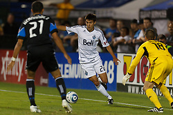 July 20, 2011; Santa Clara, CA, USA;  Vancouver Whitecaps midfielder Shea Salinas (22) dribbles past San Jose Earthquakes goalkeeper Jon Busch (18) during the second half at Buck Shaw Stadium. Salinas was credited with an assist on the play. San Jose tied Vancouver 2-2.