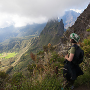 A woman looks down on Cirque de Mafate and Mafate VIllage from Col du Taibit Pass. This small French village is only accessible by foot or by helicopter.