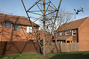 The steel girders of an electricity pylon stands close between housing on an estate in Beckton, East London.