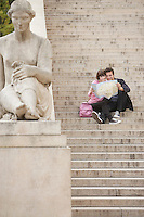 Young couple looking at map sitting on stairway