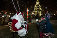 """Santa and Mrs. Claus greet children in Stewart Park following the """"Light Up Laconia"""" Holiday Parade and tree lighting Sunday evening.  (Karen Bobotas/for the Laconia Daily Sun)"""