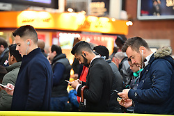 © Licensed to London News Pictures. 14/12/2016. London, UK. Stranded  and delayed passengers check their phones at Victoria Station in London on 14 December 2016, as hundreds of thousands of rail passengers face a second day of a 3 day all-out strike in an escalating dispute over the role of conductors between Southern Rail and the RMT Union. Photo credit: Ben Cawthra/LNP