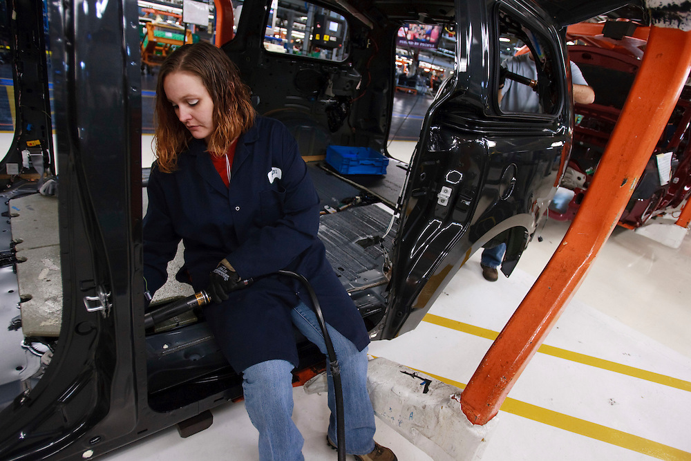 A worker on the production line at Chrysler's assembly plant in Windsor, Ontario, works on one of their new minivans as the company celebrated the production launch of the new Dodge Grand Caravan and Chrysler Town and Country, January 18, 2011.<br /> The Canadian Press/GEOFF ROBINS