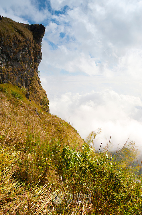 The sheer cliff of Phu Chi Fa, in Thoeng, Chiang Rai, Thailand. The cliff top is in Thailand but the plains in the right of the photograph are in Laos.