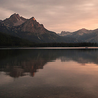 A lone fisherman rafts Stanley Lake in the Sawtooth's during a smokey sunset. Idaho