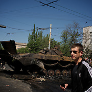 A local man passes by a military tank, set alight hours after deadly clashes between separatists armed groups and the Ukrainian Army over the control of key buildings in the city.