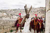 """MATERA, ITALY - 5 OCTOBER 2019: Yvan Sagnet (34, center), a political activist and former exploited tomato farmer, performs a scene of the Via Crucis in the role of Jesus Christ during the production of """"The New Gospel"""", a film by Swiss theatre director Milo Rau, in Matera, Italy, on October 5th 2019.<br /> <br /> Theatre Director Milo Rau filmed the Passion of the Christ  under the title """"The New Gospel"""" with a cast of refugees, activists and former actors from Pasolini and Mel Gibson's films.<br /> <br /> The role of Jesus is performed by Yvan Sagnet, a Political activist born in Cameroon and who worked on a tomato farm when in 2011 he revolted against the system of exploitation and led the first farm workers' strike in southern Italy. In a series of public shoots in the European Capital of Culture Matera, Jesus will proclaimed the Word of God, was crucified (October 6th 2019) and finally rose from the dead in Rome, the capital of Catholic Christianity and seat of one of the most xenophobic governments in Europe (October 10th 2019).<br />  <br /> Parallel to the film, the humanistic message of the New Testament was transformed into the present: at the beginning of September, the campaign """"Rivolta della Dignità"""" (Revolt of Dignity), which demanded fair working and living conditions     for refugees, global freedom of travel and civil rights for all, started with a march from the southern Italian refugee camps. """"It's about putting Jesus on his feet,"""" director Milo Rau said. Led by Jesus actor Yvan Sagnet, the campaign fights for the rights of migrants who came to Europe via the Mediterranean to be enslaved by the Mafia in the tomato fields of southern Italy and to live in ghettos under inhumane conditions. The campaign and the film thus create a """"New Gospel"""" for the 21st century, a manifesto of solidarity with the poorest, a revolt for a more just and humane world."""