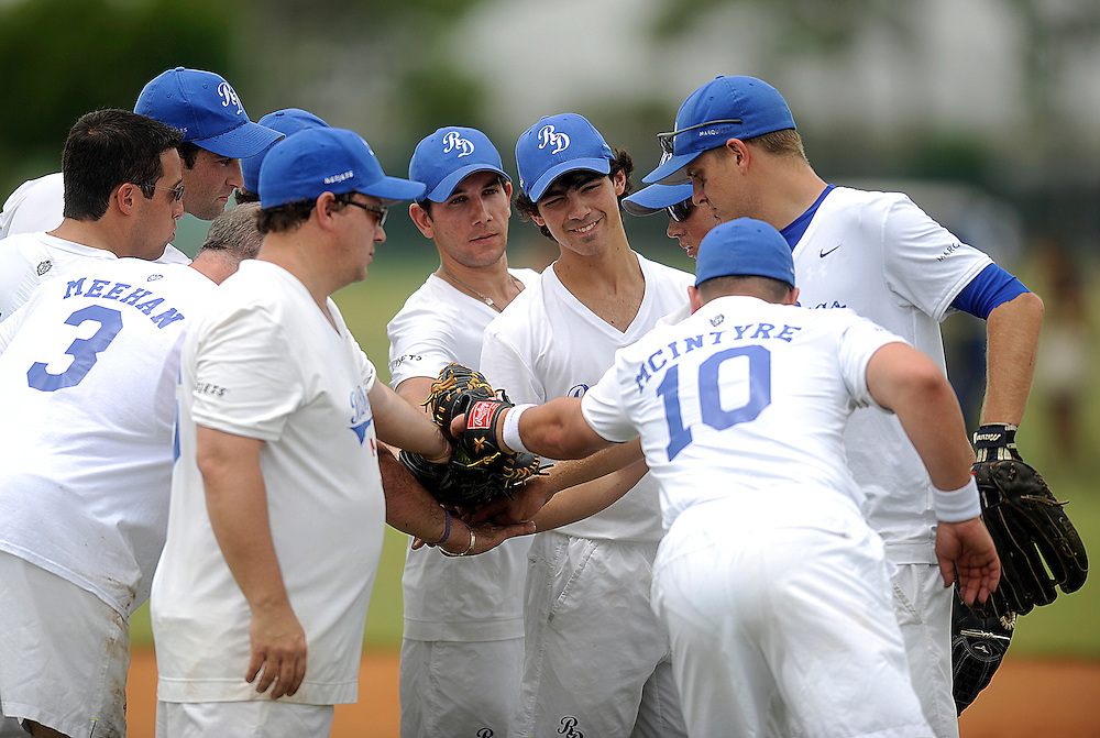 "AUGUST 19, 2009 BOCA RATON FLORIDA- Joe Jonas, of the Jonas Brothers, cheer with their teammates before the start of their  game against the Marquis Flyers. The Jonas Brothers and their team, the ""Road Dogs"" took part in the softball game which was being held by Marquis Jet at the Saint Andrews School in Boca Raton, Fla. Marquis Jet has held 9 other softball games around the country as their company team the ""Marquis Flyers"" competes in for fun games against various teams. PHOTO BY JOSH RITCHIE"