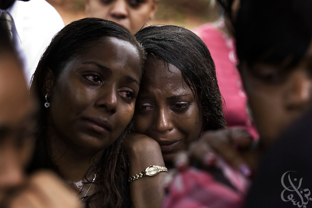 Family members mourn during the funeral of slain Jamaican Constabulary Force (JCF) officers Cornel Grant and Delano Lawrence June 15, 2008 at the Dovecot Cemetery in Spanish Town, Jamaica. Delano and Grant were gunned down in an ambush in the inner city Trench Town area of Kingston while on patrol May 23, 2008.