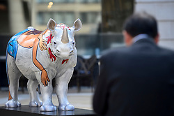 **CAPTION CORRECTION - Rhino statues are 750mm tall, not 750cm tall, as stated in previous captions**<br /> © Licensed to London News Pictures. 20/08/2018. LONDON, UK. An office worker views 'Marjorie', a rhino painted by Eileen Cooper, in Paternoster Square.  At 750mm tall and weighing 300 kg, each rhino has been specially embellished by an internationally renowned artist.  21 rhinos are in place at a popular location in central London, forming the Tusk Rhino Trail, until World Rhino Day on 22 September to raise awareness of the severe threat of poaching to the species' survival.  They will then be auctioned by Christie's on 9 October to raise funds for the Tusk animal conservation charity.  Photo credit: Stephen Chung/LNP