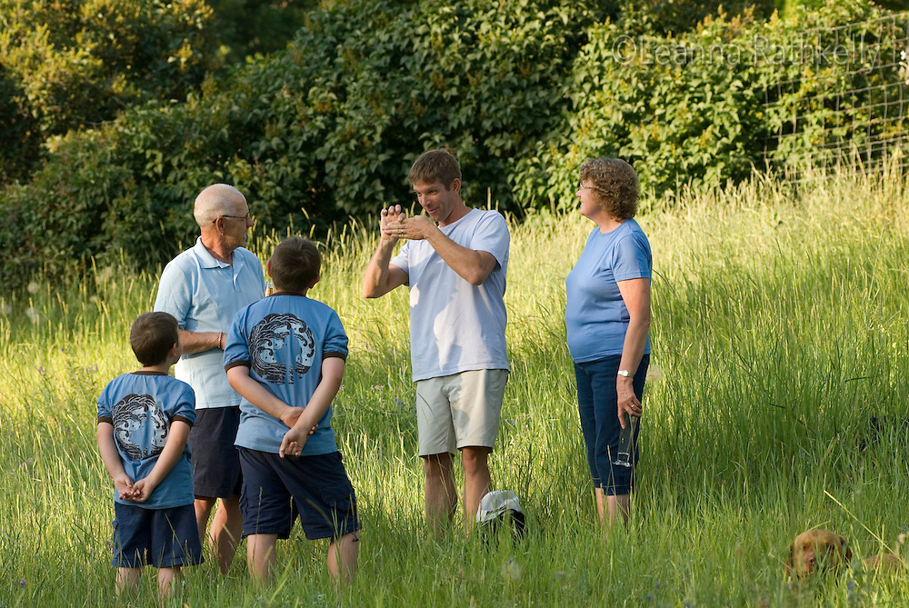 Family hangs out and tells jokes to each other in a field, Okanagan Centre, BC Canada.