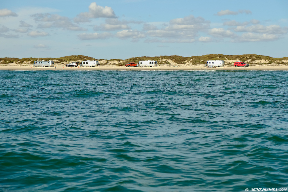 A row of recreational vehicles camp along the beach of South Padre National Seashore, Texas.