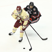Kevin Hayes #12 of the Boston College Eagles and Braden Pimm #14 of the Northeastern Huskies fight for the puck during The Beanpot Championship Game at TD Garden on February 10, 2014 in Boston, Massachusetts. (Photo by Elan Kawesch)