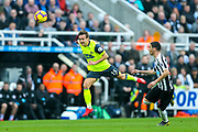 Chris Lowe (#15) of Huddersfield Town heads the ball back to his goalkeeper under pressure from Miguel Almiron (#24) of Newcastle United during the Premier League match between Newcastle United and Huddersfield Town at St. James's Park, Newcastle, England on 23 February 2019.