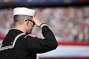 A U.S. Navy member of the military salutes during the playing of the National Anthem as part of the Salute to Service initiative before the New England Patriots 2015 week 9 regular season NFL football game against the Washington Redskins on Sunday, Nov. 8, 2015 in Foxborough, Mass. The Patriots won the game 27-10. (©Paul Anthony Spinelli)