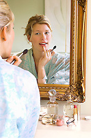 Woman in bathrobe sitting Applying Make-up looking in mirror
