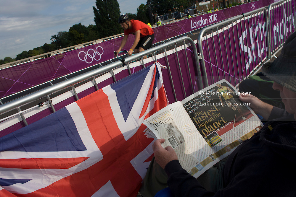 Spectator reads a tablid story written by Kamacain sprinter Eusain Bolt as a cyclist passes by before racers arrive on the first day of competition of the London 2012 Olympic 250km mens' road race. Starting from central London and passing the capital's famous landmarks before heading out into rural England to the gruelling Box Hill in the county of Surrey. Local southwest Londoners lined the route hoping for British favourite Mark Cavendish to win Team GB first medal but were eventually disappointed when Kazakhstan's Alexandre Vinokourov eventually won gold.