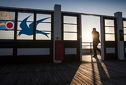 © Licensed to London News Pictures. 10/10/2018. Worthing, UK. A man walks on Worthing Pier at sunrise on a day when unseasonably high temperatures expected in parts of the UK. Photo credit: Peter Macdiarmid/LNP