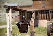 Rusty old pail hangs above an abandoned well in the wild west ghost town of Bodie, California. The former boom town is now a National Historic Landmark.