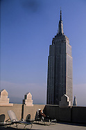 new York. young woman reading a newspaper on a rooftop terrace in front the empire state building panorama MANHATTAN  /  jeune femme lisant le journal sur une terrasse devant l empire state building panorama MANHATTAN  New york  Etats unis