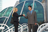 Businessman and woman shaking hands in front of office building