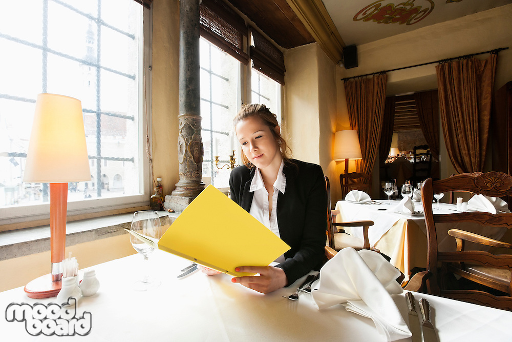 Beautiful customer reading menu at restaurant table